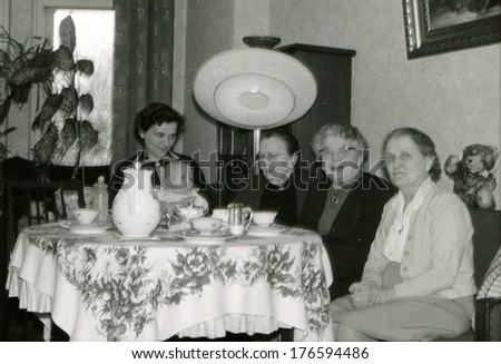 GERMANY - CIRCA 1960s: An antique photo of Three mature women and young mother with baby posing at a table covered with a cloth, on which stands the tea set