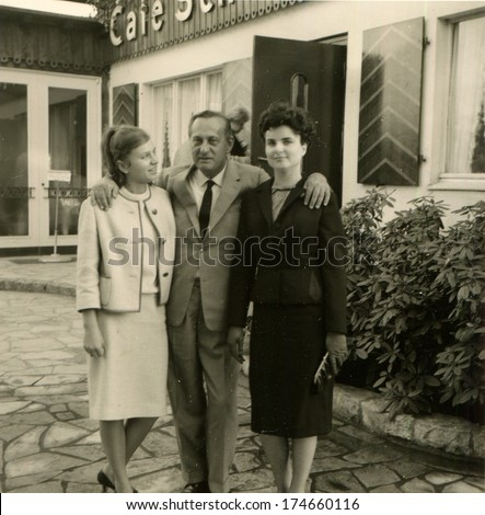 GERMANY -  CIRCA 1960s: An antique photo shows man in a business suit hugging the shoulders of two elegant women in front of the cafe
