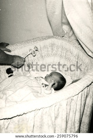 GERMANY - CIRCA 1960s: man's hand holds out a rattle baby lying in the cradle - stock photo