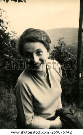 GERMANY - CIRCA 1960s: smiling woman looking at the camera, leaning forward against the backdrop of the mountains
