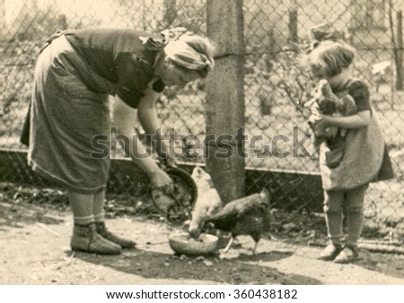 GERMANY, CIRCA THIRTIES: Vintage photo of little girl feeding poultry