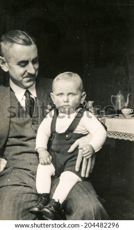 GERMANY, CIRCA TWENTIES - Vintage photo of father and little son - stock photo