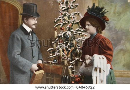 GERMANY - CIRCA 1915: Vintage christmas card printed in Germany in 1915 with loving couple beside a christmas tree with presents, circa 1915. - stock photo