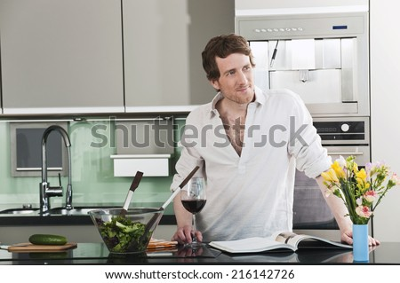 Germany, Hamburg, Man in kitchen preparing salad