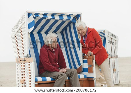 Germany, North Sea, St.Peter-Ording, senior couple man resting on hooded beach chair woman standing on side - stock photo