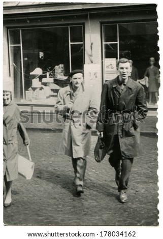 GERMANY -  1970s: An antique photo shows Two young men in raincoats cross the street