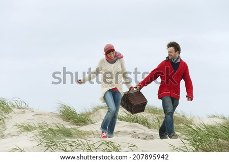 Germany St.Peter-Ording North Sea couple holding picnic basket walking on beach - stock photo