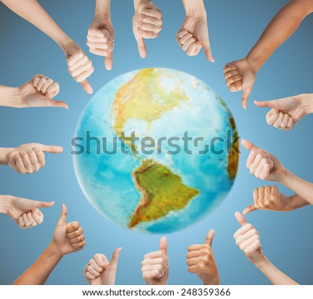 gesture and body parts concept - human hands showing thumbs up in circle over earth globe and blue background - stock photo