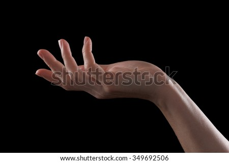 Gesture beautiful hand of a young girl, palm open up. Isolated on black background - stock photo