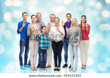 gesture, family, generation and people concept - group of smiling men, women and boy showing ok hand sign over blue holidays lights background - stock photo