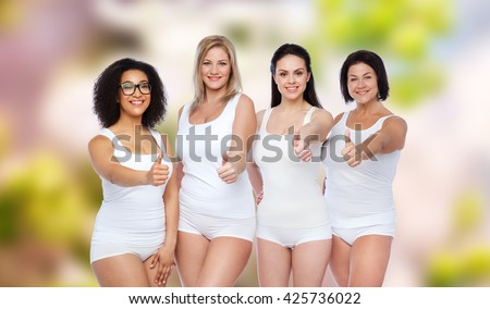 gesture, friendship, beauty, body positive and people concept - group of happy different women in white underwear showing thumbs up over natural spring background - stock photo