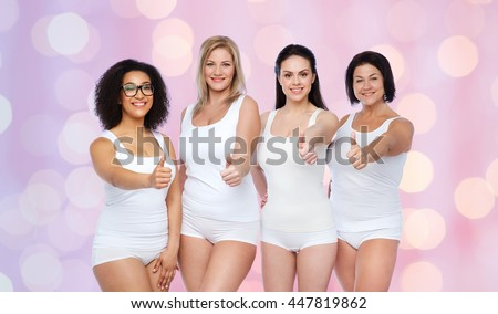 gesture, friendship, beauty, body positive and people concept - group of happy different women in white underwear showing thumbs up over rose quartz and serenity lights background - stock photo