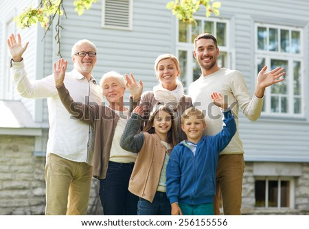 gesture, happiness, generation, home and people concept - happy family waving hands in front of house outdoors - stock photo