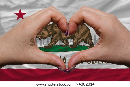 Gesture made by hands showing symbol of heart and love over us state flag of california - stock photo