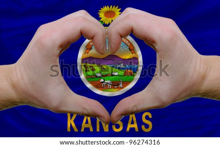 Gesture made by hands showing symbol of heart and love over us state flag of kansas - stock photo