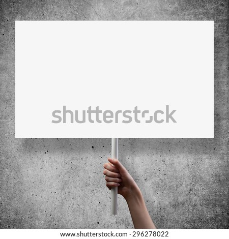 gesture of hand holding a blank white paper over cement background - stock photo