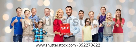 gesture, sale, shopping and people concept - group of smiling men, women and kids showing thumbs up and holding red sale sign or banner over holidays lights background