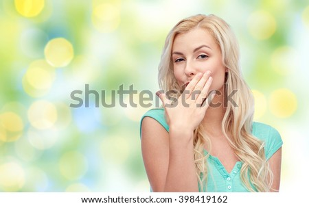 gesture, summer and people concept - smiling young woman or teenage girl covering her mouth with hands over green lights background - stock photo