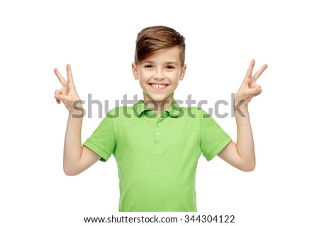 gesture, triumph, childhood, fashion and people concept - happy smiling boy in green polo t-shirt showing peace or victory hand sign - stock photo