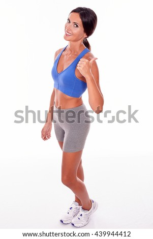 Gesturing brunette woman with a toothy smile looking at the camera while wearing blue and grey casual clothing and her hair tied back, isolated - stock photo