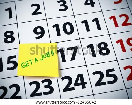 Get a job written on a sticky note on a calendar. - stock photo