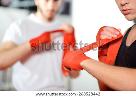 Get prepared to the fight. Athletic guys pulling on hands red boxing bandages - stock photo