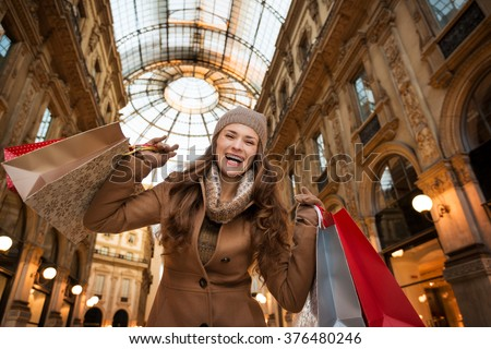 Get ready to making your way through shopping addicted crowd. Huge winter sales in Milan just started. Happy young woman with shopping bags in Galleria Vittorio Emanuele II rejoicing - stock photo