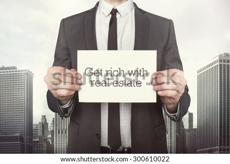 Get rich with real estate on paper what businessman is holding on cityscape background