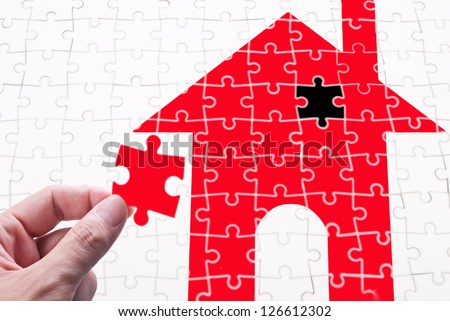 Get your house concept. Finish the goal of own a house. human hand with puzzle piece - stock photo