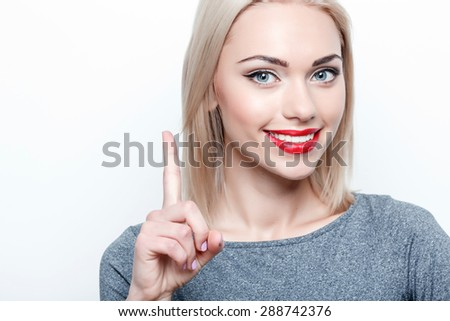 Getting idea. Cheerful young woman standing on white isolated background and pointing upwards with her index finger - stock photo