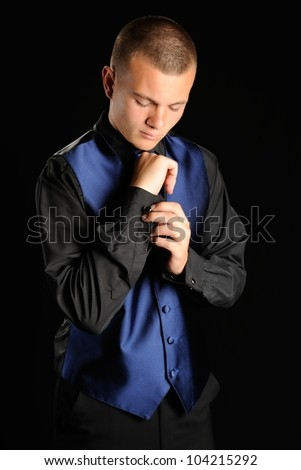 Getting Ready for Prom. Teenage boy getting ready for prom date in front of a black background. - stock photo