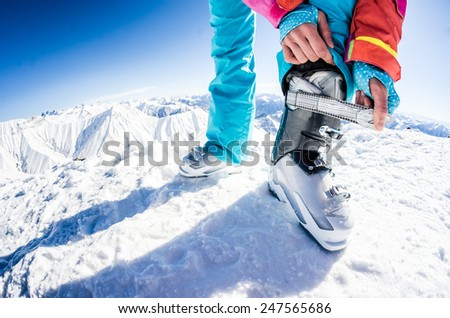 getting ready for skiing, fastening the boots - stock photo