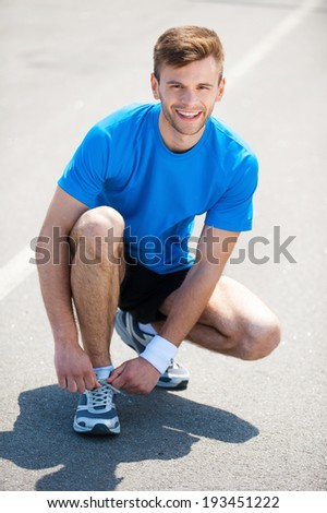 Getting ready to jogging. Top view of man tying shoelaces on sports shoe and smiling while standing outdoors  - stock photo