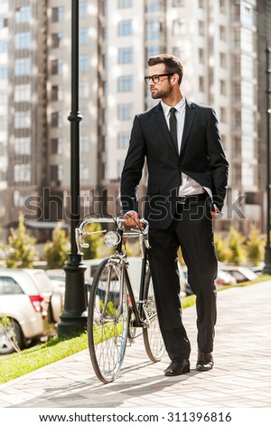 Getting to work by bike today. Full length of handsome young businessman rolling his bicycle while walking outdoors - stock photo