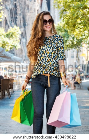 Getting unique trends of Barcelona. Happy fashion-monger woman with shopping bags walking down the street - stock photo