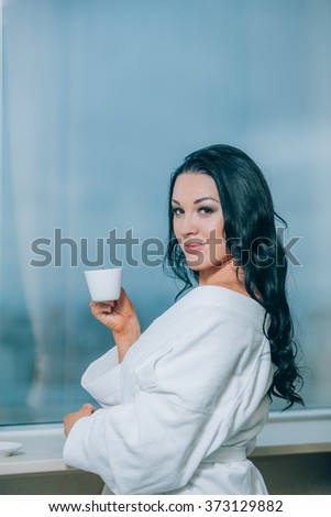 Getting warm with fresh coffee. Beautiful young woman in white bathrobe drinking coffee and looking through a window - stock photo