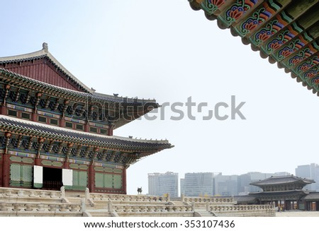 Geunjeongjeon building in Gyeongbokgung Palace with atb the background offices in midtown Seoul - stock photo