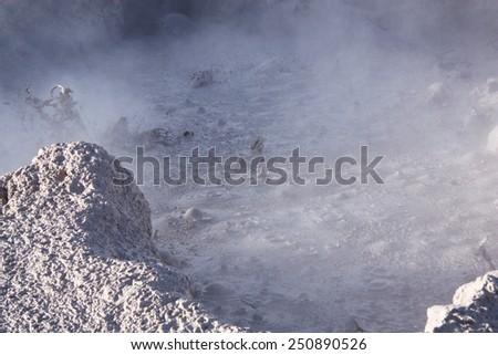Geyser with boiling mud in the natural reserve Reserva de Fauna Andina Eduardo Avaroa in Bolivia - stock photo