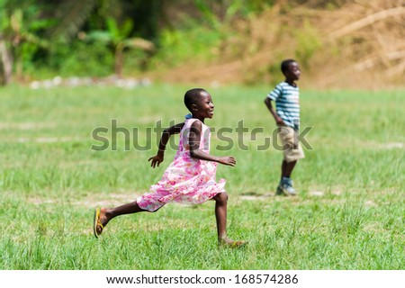 GHANA - MARCH 3, 2012: Unidentified Ghanaian girl runs happily in the