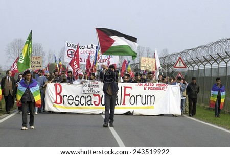 GHEDI, ITALY-MARCH 29, 2003: demonstrators protest on a rally against the war along the wire fence outside a military base, in Ghedi. - stock photo