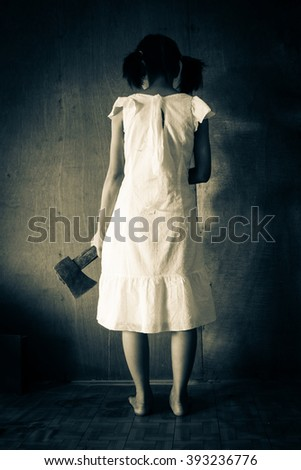Ghost girl in haunted house,Mysterious girl in white dress standing in abandon house carrying an axe in front of the wall - stock photo