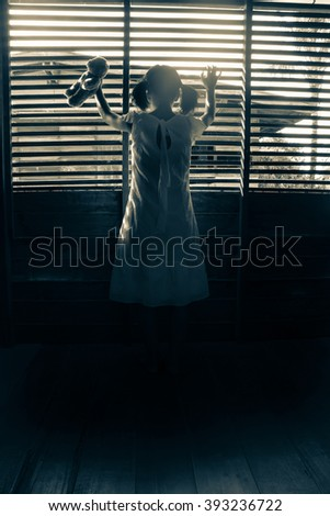 Ghost girl in haunted house,Mysterious girl in white dress standing in abandon house holding hand on the window  - stock photo