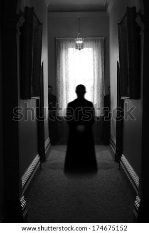 Ghostly apparition hovering in a dimly lit eerie corridor for Halloween concept.  - stock photo
