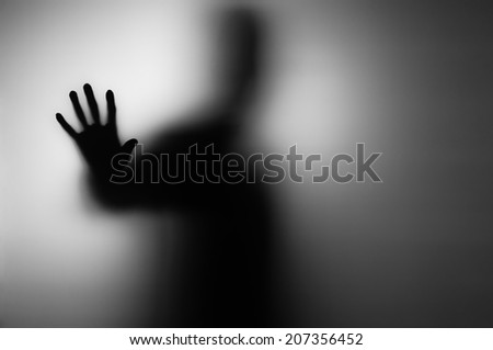 Ghosts hand silhouette behind the frozen glass. - stock photo