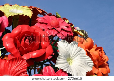 Giant colorful plastic flowers arranged spherically on a clear blue sky - stock photo