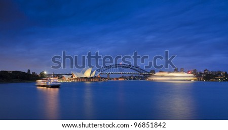 Giant cruise liner enters Sydney harbour passes house and harbour bridge at sunrise with lights and blurred motion - stock photo