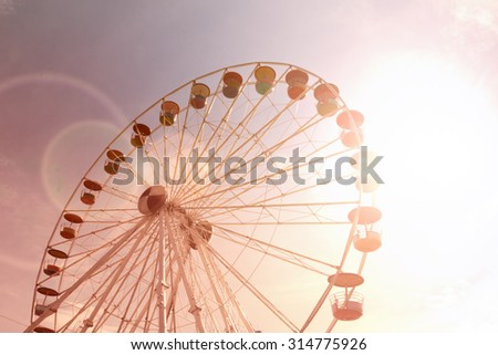 Giant ferris wheel against blue sky faded color version - stock photo