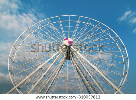 Giant ferris wheel structure under construction without passenger cage over blue sky and white cloud