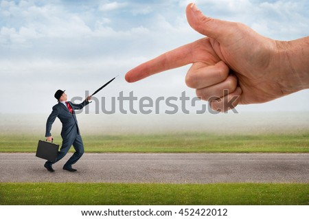 giant finger pointing aggressively at a defensive businessman - stock photo