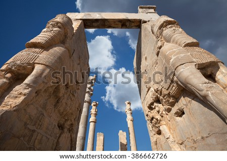 Giant lamassu statues guarding Gate of All Nations, against blue sky with dramatic bright white clouds in ancient Persepolis, capital of Achaemenid Empire in Shiraz, Iran. - stock photo